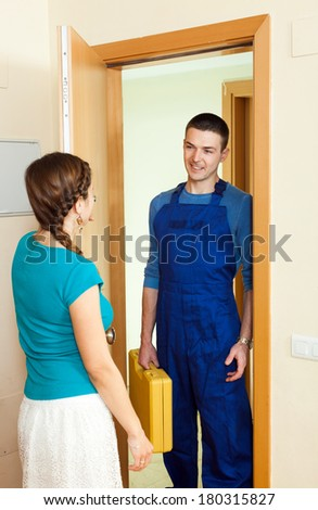 Young housewife  meeting happy repairman  at the door at home - stock photo