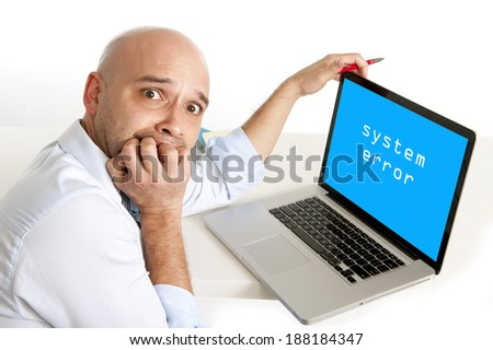 young latin worried business man biting finger nails in anxiety and stress working at the office on computer with fatal system error in technology and technical problems - stock photo