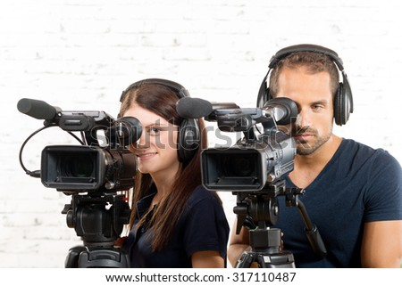 young man and woman with professional video cameras - stock photo
