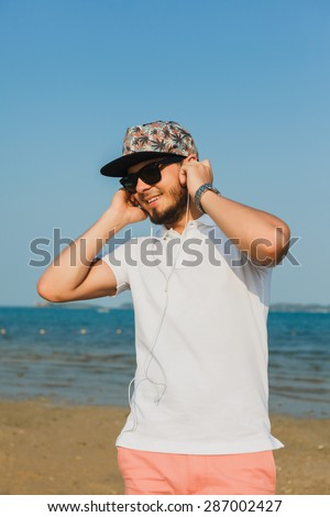 young man in a cap and sunglasses who listens to the music of the sea - stock photo