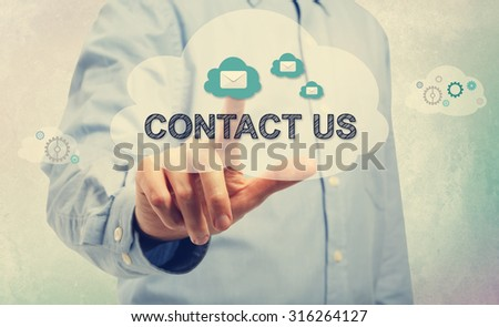 Young man in blue shirt pointing at Contact Us - stock photo