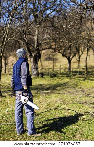Young  man ready to  cut down trees with chainsaw in the garden - stock photo