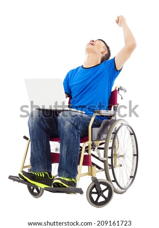 young man sitting on a wheelchair and  excited to raise arm - stock photo