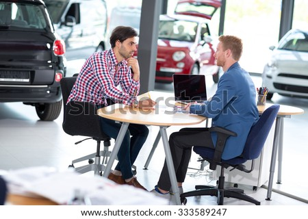 Young man talking with car dealer, listens benefits in buying - stock photo