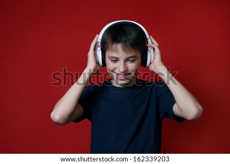 young man teen listening to music on headphones red background - stock photo