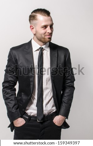 Young man with short hair and stubble wears a dark suit and a narrow tie. He has his hands casually in his pockets and looks into the distance. Isolated against a gray background. - stock photo