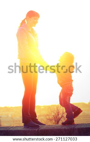 Young mother and son holding hands and laughing standing on the parapet on the background of the backlight. Family Vintage composition - stock photo