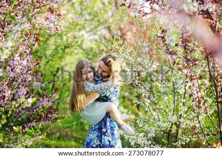 ? young mother playing with her daughter in the lush spring garden - stock photo