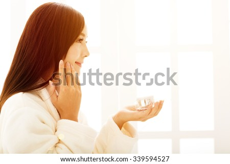 young woman doing  makeup in front of  bathroom mirror at morning - stock photo
