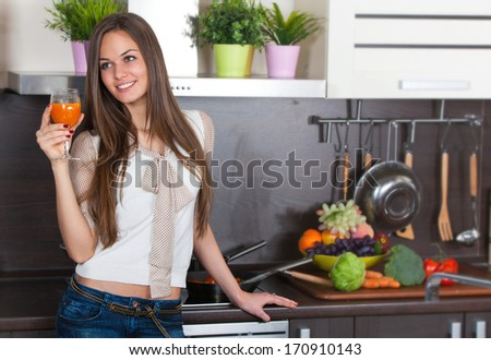 Young woman drinking fresh juice in the domestic kitchen - stock photo