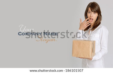 Young woman holding a brown parcel with a surprised expression  - stock photo