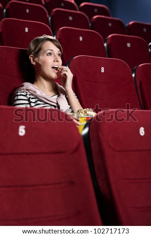 Young woman in the cinema hall side view - stock photo