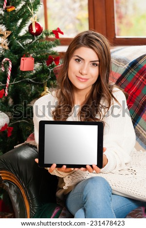 Young woman sitting on couch, alone, in front of christmas tree on living room,showing tablet pc with copy-space - stock photo