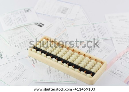 A abacus with receipt, household bills - stock photo