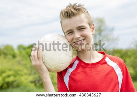 A Active happy boy, having fun outdoor, playing football in sportive summer - stock photo