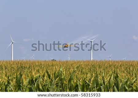 A agricultural plane dusts crops against a blue sky - stock photo