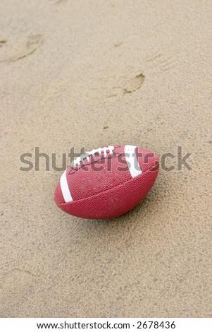 A American football on the beach in the rain - stock photo