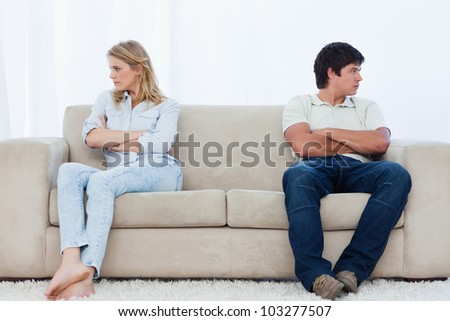 A angry couple sit at the two ends of the couch with their arms folded looking away - stock photo