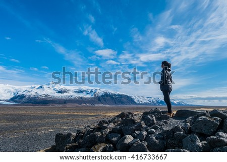 A asian girl is looking at the view along the Iceland's road. - stock photo