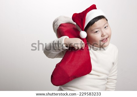 A asian(korea, japan, chinese, china) boy hold(hug) christmas socks for presents and wearing christmas hat with big smile isolated white at the studio. - stock photo