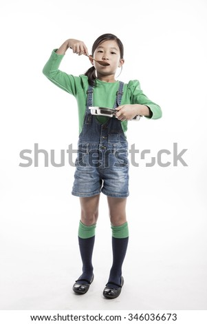 A asian(korea, japanese, chinese) girl(kid, student, child, woman, female) wearing green shirts and denim pants hold a stainless food tray and wood spoon for breakfast(lunch, dinner) isolated white. - stock photo
