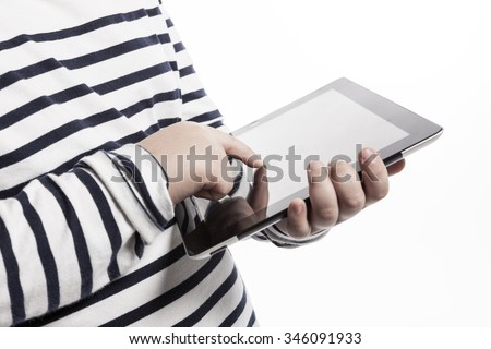 A asian(korean, japanese, chinese) boy(kid, student, child, man, male) wearing white stripe shirts and blue denim hold and watch(see, touch) a digital device(pad, mobile, note) isolated white. - stock photo