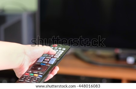 A asian women watching TV and using remote controller, Technology background concept - stock photo