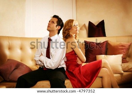 a attractive, young and rich couple is sitting on a lounge and have an argue - stock photo