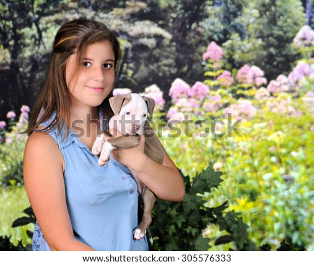 A attractive young teen happily holding her new pitbull puppy on a beautiful, sunny spring day.   - stock photo