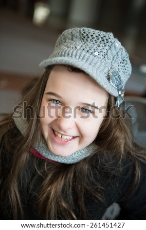 A attractive young tween dressed in winter coat and wool hat smiles at the camera.   - stock photo