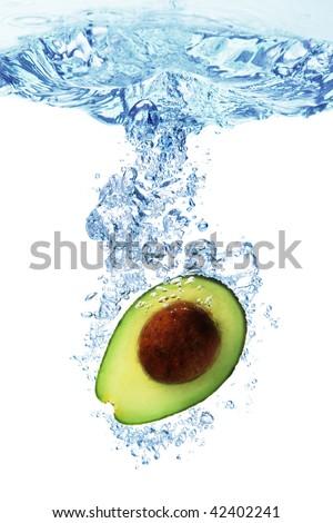 A Avocado splashing into water against a white background. - stock photo