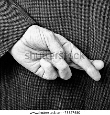 A B/W conceptual image of a business man with his fingers crossed behind his back. - stock photo