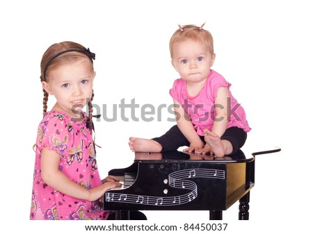 A baby and another girl play with a piano. - stock photo