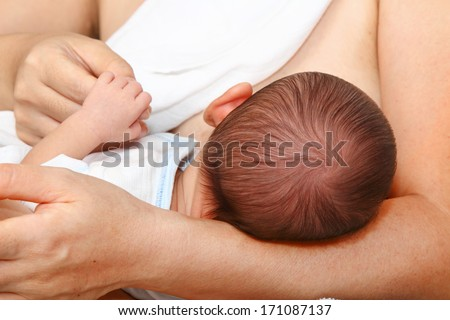 A baby being breastfed - stock photo