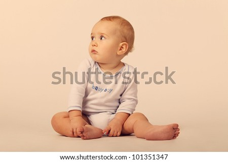 A baby boy in a blue and white bodysuit with a sign Baby Boy, sitting on the floor on the white background - stock photo