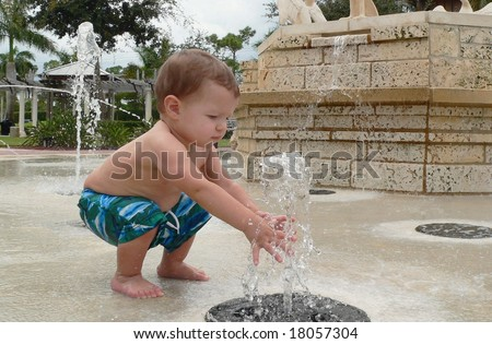 A baby boy playing in a water fountain at a park. His hand are in the water that is bubbling up from the outdoor fountain. He is wearing blue swim trunks. He is squatting down to reach the water. - stock photo