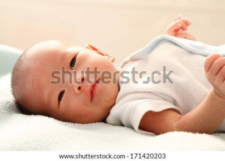 A baby boy smiling on a bed - stock photo