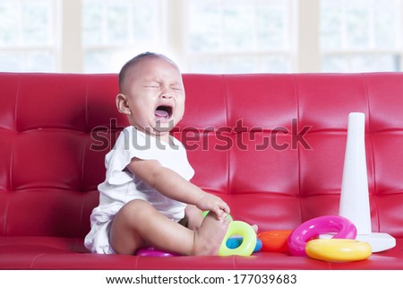 A baby girl crying with toys on sofa - stock photo