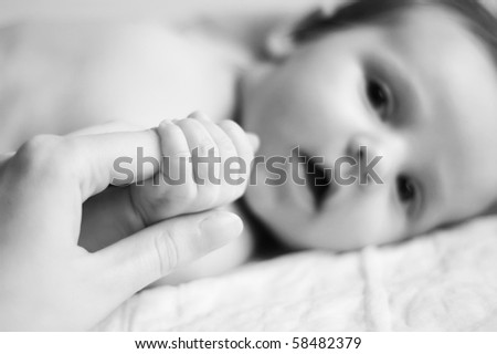 A baby holding a finger of his parents - shallow dof - stock photo