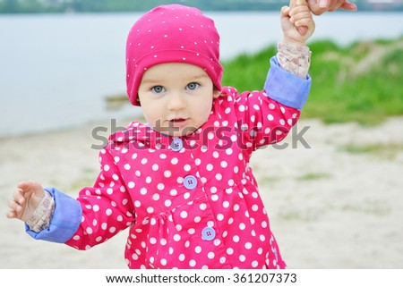 A baby in hat with dots on the background of nature. Child near the lake. Kid walking on the street in the spring. Spring scene with little girl. Summertime, springtime Concept of childhood - stock photo