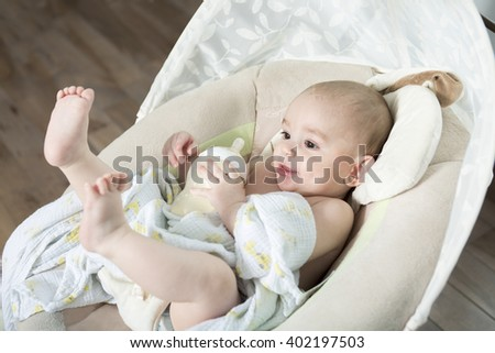 A baby inside the house having good time - stock photo