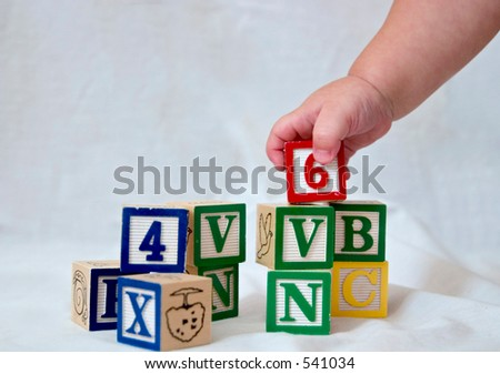 a baby's hand picking up a block - stock photo