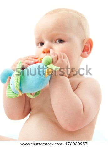A baby with a soft toy in the hands being held to the mouth. - stock photo