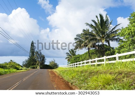 A back country road in a remote part of Kauai, Hawaii with beautiful green grass and a white fence lining the roadway. - stock photo