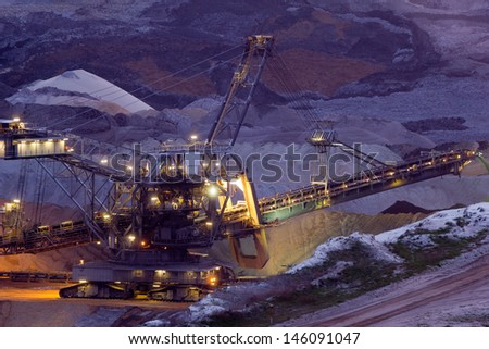 A back-filling machine in an open coal mine at night - stock photo