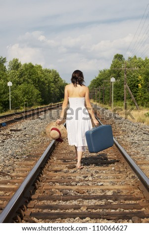A back view of a young woman leaving with suitcase, hat and the clothes on her back. - stock photo