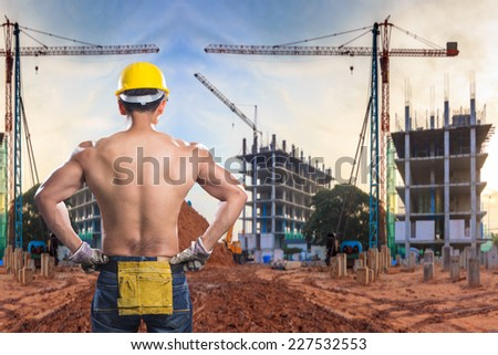 a back view of construction worker showing his muscles at building construction site and sunset sky with crane construction - stock photo