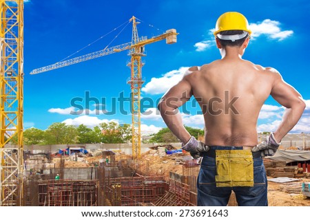 a back view of construction worker showing his muscles at footing of building construction site with tower crane and blue sky - stock photo