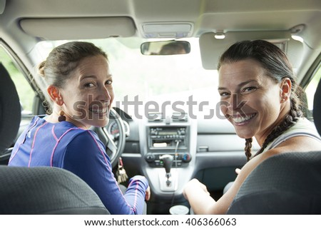 A Back view of two friends on a car  - stock photo