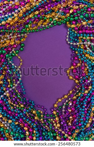 A background of mardi gras beads with copy space - stock photo